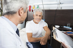 Senior Patient Looking At Doctor In Rehab Center stock photography