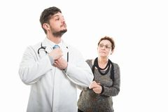 Senior patient looking at male doctor arranging tie. Isolated on white background Stock Images