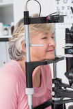 Senior patient looking into slit lamp Royalty Free Stock Photos