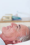 Senior patient lying on a hospital bed Stock Images