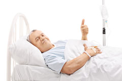 Senior patient lying in hospital bed and giving thumb up Royalty Free Stock Photography