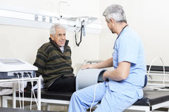 Senior Patient Receiving Electromagnetic Therapy. Smiling senior patient looking at doctor receiving relectromagnetic therapy stock images