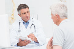 Senior patient sharing problems with doctor Stock Photos