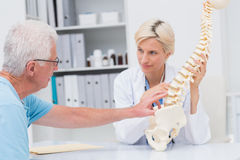 Senior patient showing spine problems to doctor at table Royalty Free Stock Image