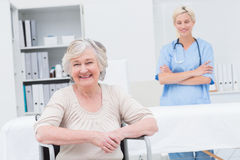 Senior patient sitting on wheelchair while nurse standing in background Royalty Free Stock Images