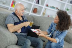 Senior patient at sofa while career giving him tea Stock Image
