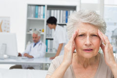 Senior patient suffering from headache with doctors at medical office royalty free stock image