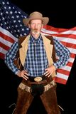 Senior patriot cowboy. Firm full-body standing senior cowboy in traditional Western outfit and wardrobe with his hands in his hips peering sternly backed by the Stock Photography