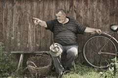 Senior peasant sitting on a bench at summer day and pointing to somewhere. Toned image of smiling Ukrainian senior peasant sitting on a bench at summer day and Stock Photo