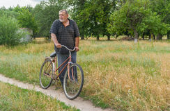 Senior peasant standing on a country road with old rusty bicycle Stock Images