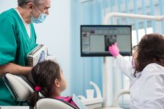 Senior pediatric dentist with assistant doing dental treatment patient girl using dental x-ray machine in dental office stock image