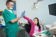 Senior pediatric dentist and happy girl after treating teeth at dental clinic office, smiling and giving high-five. Dentistry, medicine, stomatology and health royalty free stock photo
