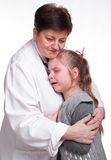 Senior pediatrician calming little girl. On a white background royalty free stock photo