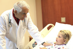 Senior Pediatrician Examining Girl In Clinic Royalty Free Stock Photos
