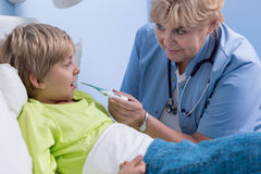Senior pediatrician taking temperature Stock Photo