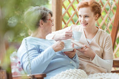 Pensioner drinking tea. Senior pensioner in glasses sitting outside and drinking tea together with hospice worker royalty free stock photo