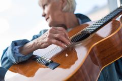 Senior Pensive Lady Playing Romantic Melody On Guitar Stock Photography