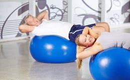 Senior people doing sit-ups in gym Stock Image
