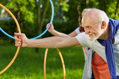 Senior people doing sports with hoops in garden Royalty Free Stock Images