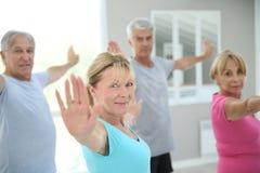 Senior people doing yoga excercises Stock Photo