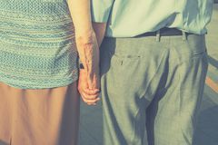 Senior people elderly couple holding hands walking in the street. Family values romantic love devotion togetherness fidelity. Concept. Touching lifestyle urban royalty free stock image