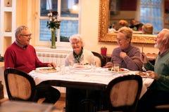Senior people enjoy and smiling while eating dinner. Group of senior people enjoy and smiling while eating dinner at nursing home stock photo