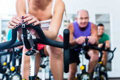 Senior people in gym spinning on fitness bike stock photo