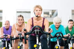 Senior people in gym spinning on fitness bike. Senior and young people spinning on fitness bike in gym doing endurance and cardio training, the instructor is Royalty Free Stock Photography