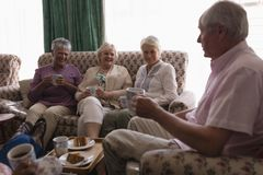 Senior people having coffee in living room. Side view of senior people having coffee and cake in living room at home royalty free stock image