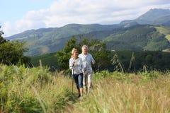 Senior people hiking in mountains Royalty Free Stock Photos