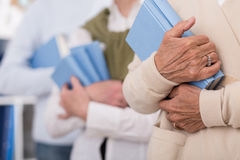 Senior people holding books. In blue cover Royalty Free Stock Photos
