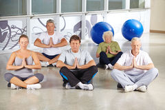 Senior people during meditation in yoga class. Group of senior people during meditation in yoga class in a gym royalty free stock photography