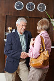 Senior people meet at hotel reception. Two senior people meet at hotel reception and shaking hands Royalty Free Stock Images
