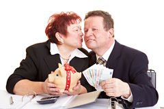 Senior people with money and piggy. Senior woman piggy bank kissing her husband who holds Euro banknotes Stock Photo