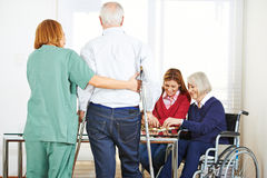 Senior people in nursing home with garegiver Royalty Free Stock Photo