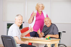 Senior people in nursing home holding thumbs up Stock Images