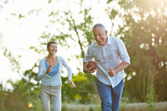 Senior people playing american football. Together outside in summer Royalty Free Stock Images