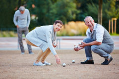 Senior people playing boule lifting up balls Stock Image