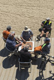 Senior people playing dominoes on the beach, Barcelona. Stock Images