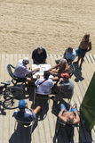 Senior people playing dominoes on the beach, Barcelona. Royalty Free Stock Photos