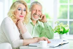 Senior people reading book. Happy senior couple sitting at table and reading book Stock Image