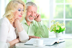 Senior people reading book. Happy senior couple sitting at table and reading book Royalty Free Stock Photography