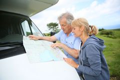 Senior people reading roadmap by camping car Royalty Free Stock Image