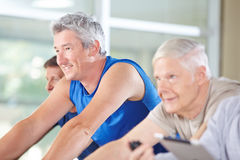 Senior people riding spinning bikes in gym Stock Images