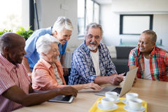 Senior people showing laptop to healthcare worker. While sitting at table in nursing home royalty free stock photo