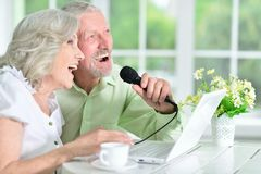 Senior people singing karaoke. Senior couple sitting at table  and singing karaoke with  laptop Royalty Free Stock Photo