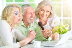 Senior people singing karaoke. Group of senior people sitting at table using laptop and singing karaoke Stock Photos