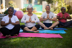 Senior people sitting in prayer position at park Royalty Free Stock Images
