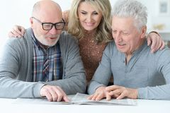 Portrait of senior people sitting at table and reading newspaper royalty free stock photography