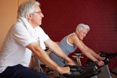 Senior people on spinning bikes Royalty Free Stock Image
